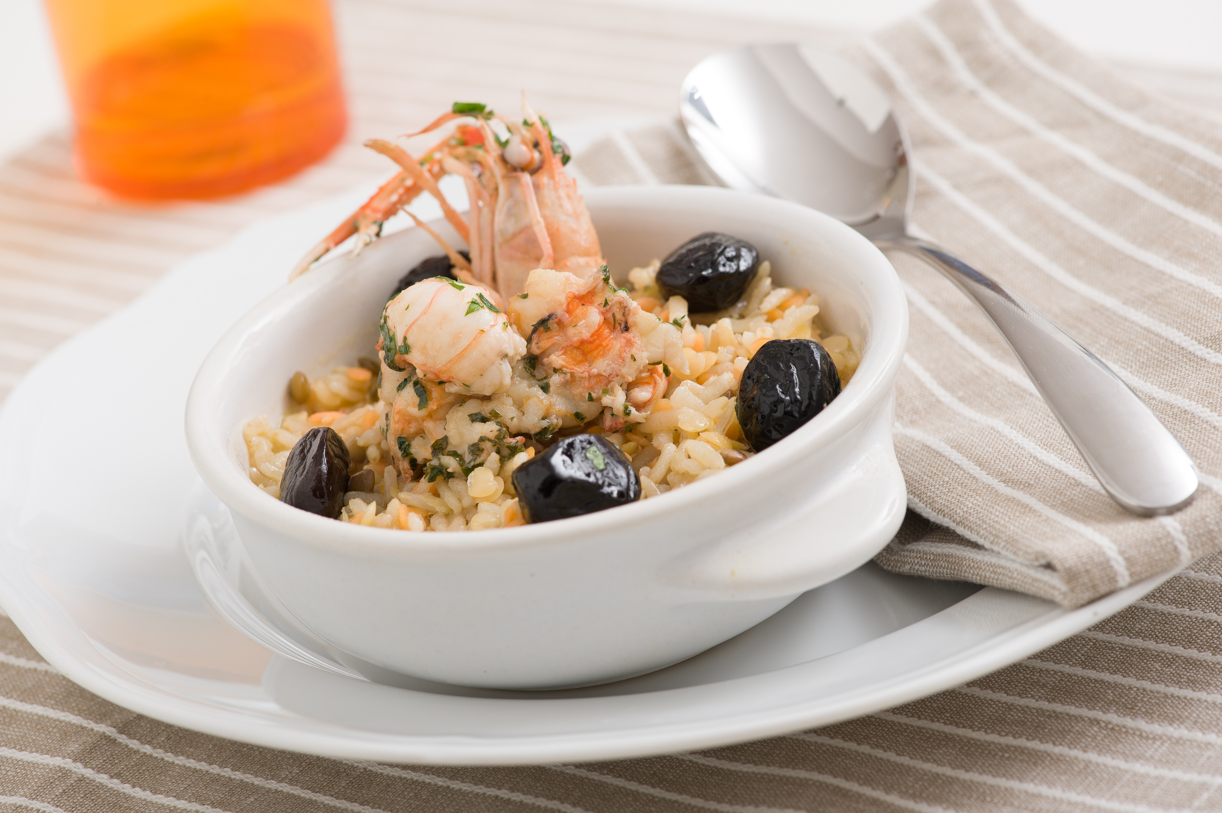 Integral rice without gluten and lentils with scampi stewed in white wine and black olives